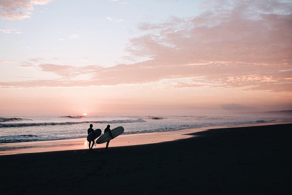 サーフボードを持つ2人夕暮れビーチ