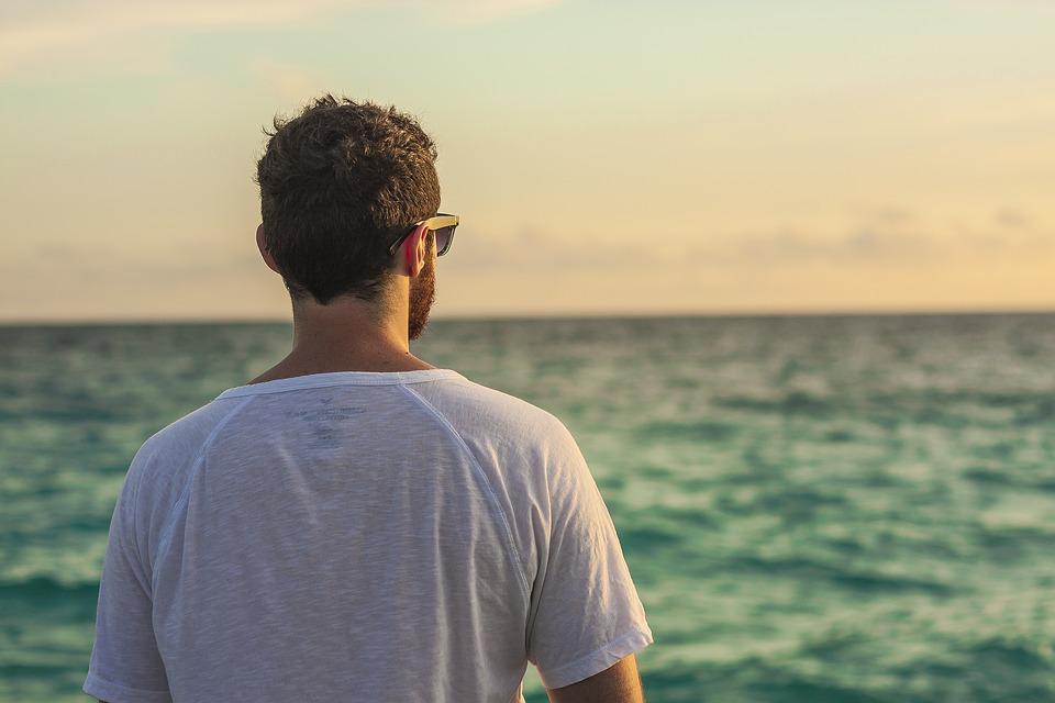 Tシャツ海を見ている男性