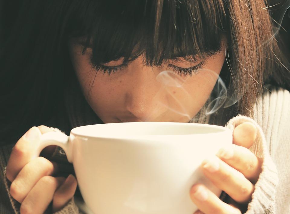 目を伏せた女性コーヒーカップ