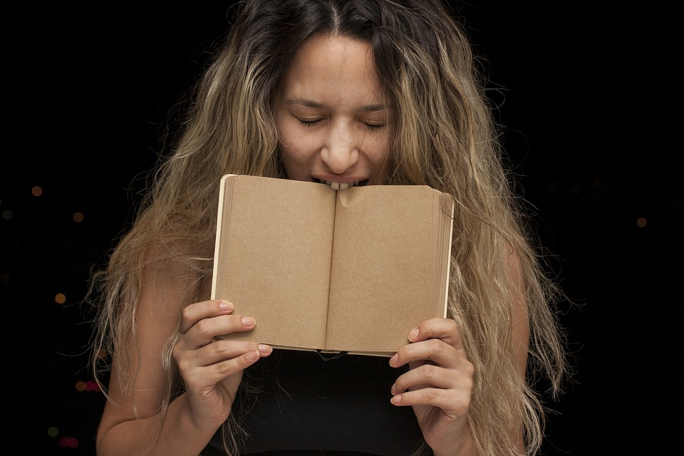 ノートをかじる女性