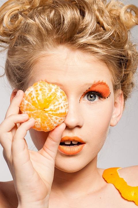 オレンジを持っている女性