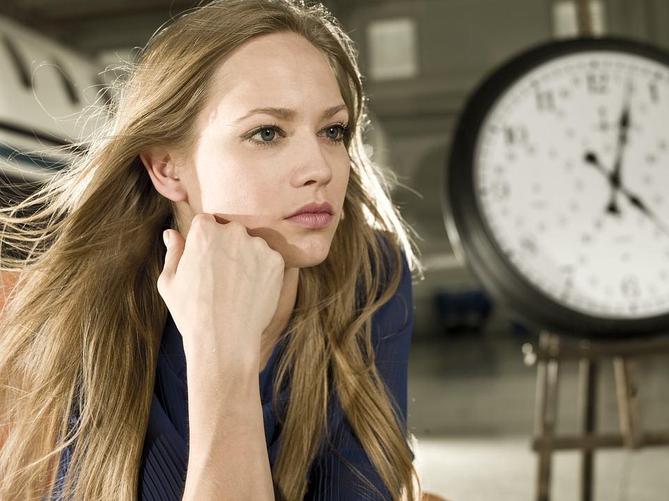 時計と髪の長い女性